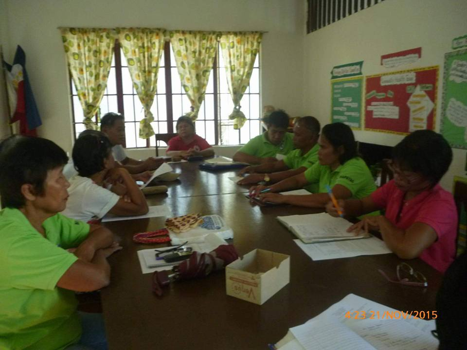 Punong Barangay Leonise O. Mierla is seen, in red shirt, seated at the head of the table during the session.
