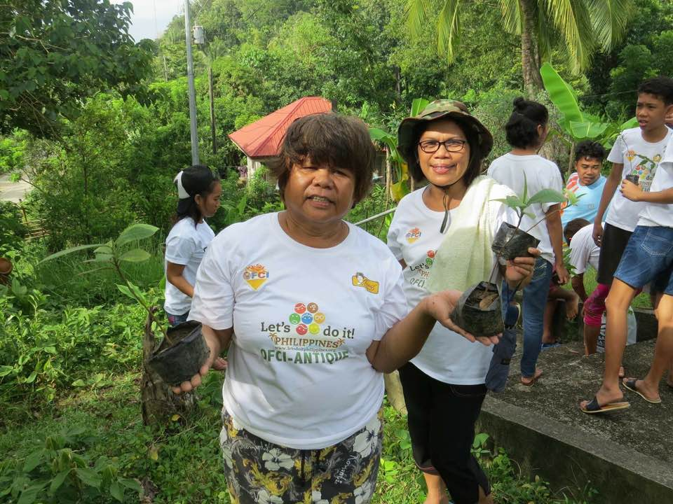 "Barangay Captain Leonisee ""Api"" O. Mierla and OFCI Antique Secretary Acay Edelmira Onifa, are shown here holding tree seedlings given by DENR, preparatory to planting."